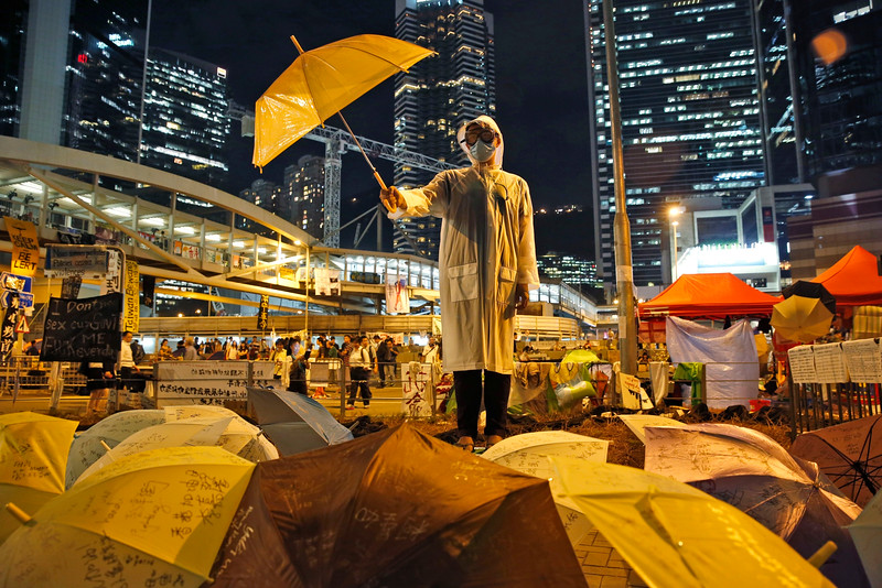 Description of  A protester holds an umbrella during a performance on a main road in the occupied areas outside government headquarters in Hong Kong's Admiralty in Hong Kong Thursday, Oct. 9, 2014. Talks between the Hong Kong government and student leaders of a democracy protest that has blocked main roads in the Asian financial hub for nearly two weeks are canceled because they're unlikely to be constructive, a senior government official said Thursday. (AP Photo/Kin Cheung)