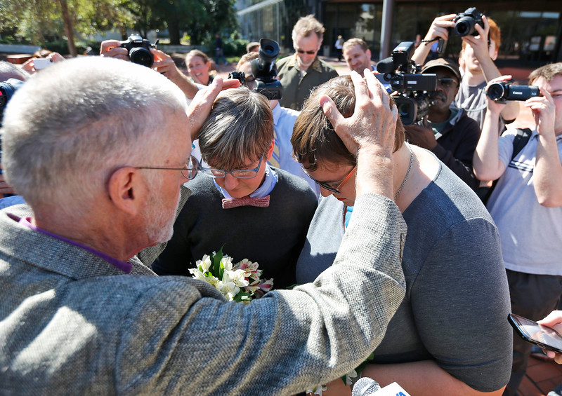 Description of  Rev. Robin Gorsline, left, marries Nicole Pries, second from left, and Lindsey Oliver, one of the first same-sex couples in Virginia to be married, Monday, Oct. 6, 2014, outside a Richmond court building in Richmond, Va. The U.S. Supreme Court's order turning away appeals from five states seeking to prohibit same-sex marriage has triggered a series of moves in affected states to clear the way for gay and lesbian unions. (AP Photo/Steve Helber)