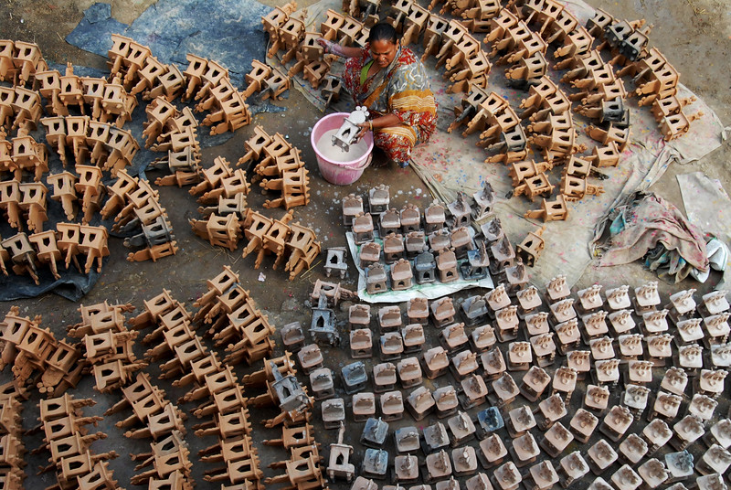 Description of  An Indian potter prepares clay lanterns used during Diwali celebrations ahead of the forthcoming Hindu festival in Jalandhar on October 8, 2014. Diwali, celebrated this year on October 23, marks the victory of good over evil and commemorates the time when the Hindu god Lord Rama achieved victory over Ravana, and returned to his kingdom of Ayodhya after 14 years exile. AFP PHOTO/SHAMMI MEHRA