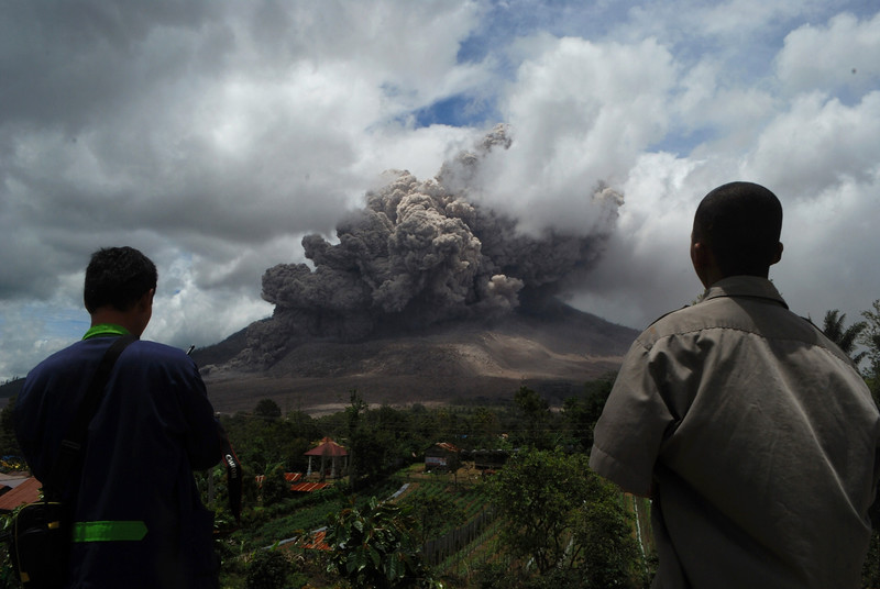 Description of  Residents watch as dark giant ash clouds rise from the crater of Mount Sinabung volcano during an eruption on October 8, 2014, as seen from Karo district located on Indonesia's Sumatra island, following an earlier eruption on October 5, 2014. According to authorities hundreds of residents are still housed at evacuation centers as authorities maintains off limit danger zone around Mount Sinabung located in Indonesia's Sumatra island following deadly eruption in early February that killed about 17 people.  AFP PHOTO / SUTANTA ADITYA