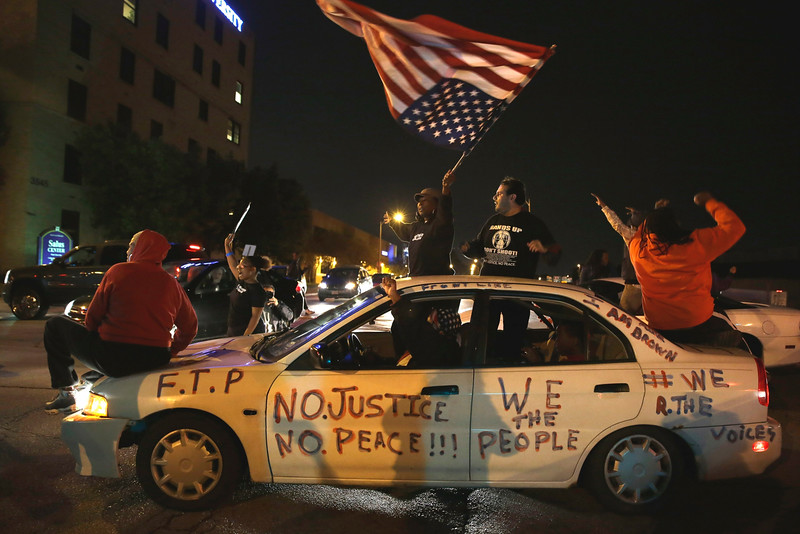 Description of  Protesters block a street Thursday, Oct. 9, 2014, a day after Vonderrit D. Myers was shot and killed by white, off-duty St. Louis police officer in St. Louis. Police say Myers was shot Wednesday after he opened fire on the off-duty officer, but Myers' parents say he was unarmed.(AP Photo/Jeff Roberson)