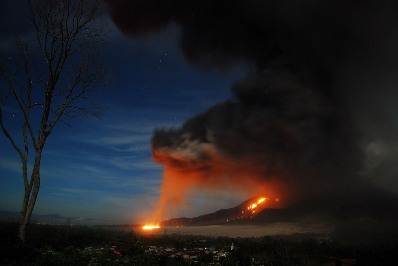 Description of  This long exposure photograph taken late on October 9, 2014 shows scorching lava flow and giant ash clouds released from the crater during the eruption of Mount Sinabung volcano as seen from Karo district located in Sumatra island. Indonesian authorities said pyroclastics flow reached 4.5 kilometers down the slope threatening populated villages whlie ash clouds reached three kilometers to the sky during it latest series of eruption that began on October 5. AFP PHOTO / Sutanta ADITYAS