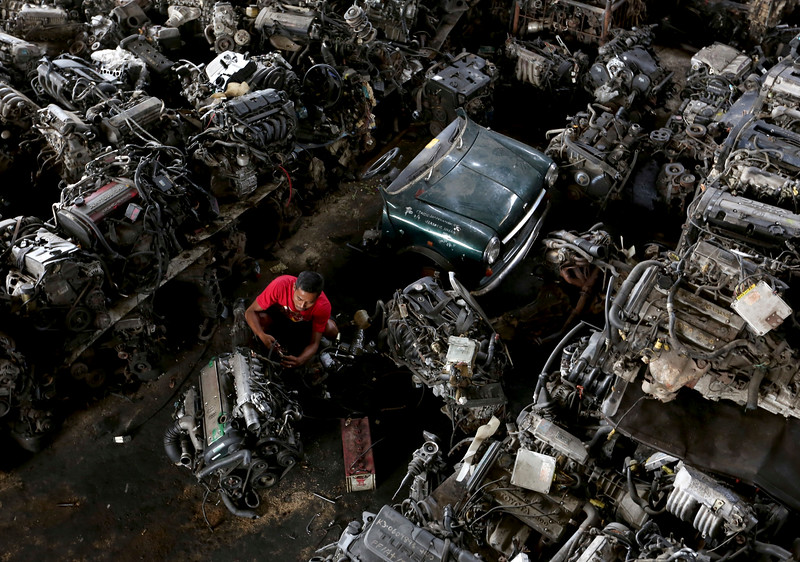 Description of  A worker repairs a car engine among automobile parts at a junkyard on the outskirts of Jakarta, Indonesia. Friday, Oct. 10. 2014. (AP Photo/Tatan Syuflana)