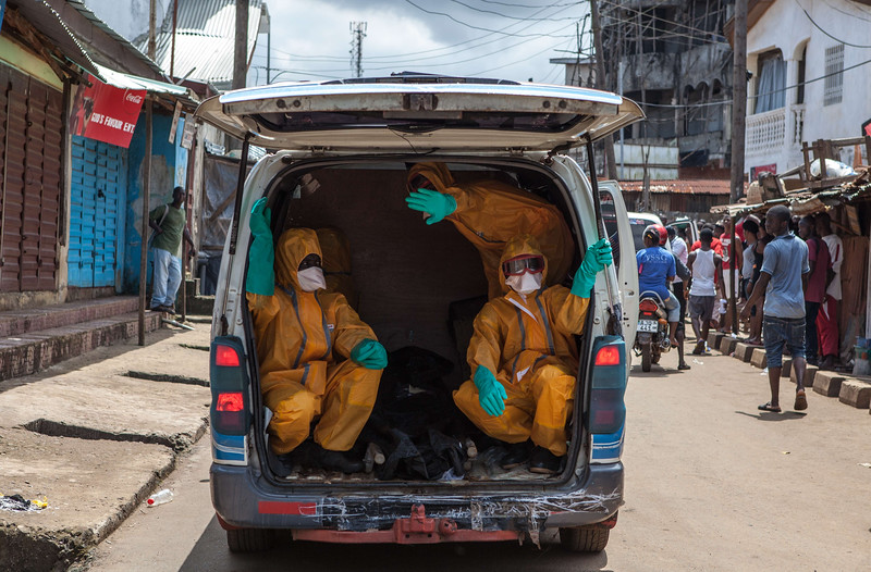 Description of  Volunteers arrive to pick up bodies of people who died of the Ebola virus, against a 100 US dollar weekly risk-taking compensation, on October 8, 2014 in Freetown. Dozens of British military personnel are due to fly to Sierra Leone next week to help build medical facilities to combat the Ebola epidemic, the defence ministry said on October 7.        AFP PHOTO/FLORIAN PLAUCHEUR