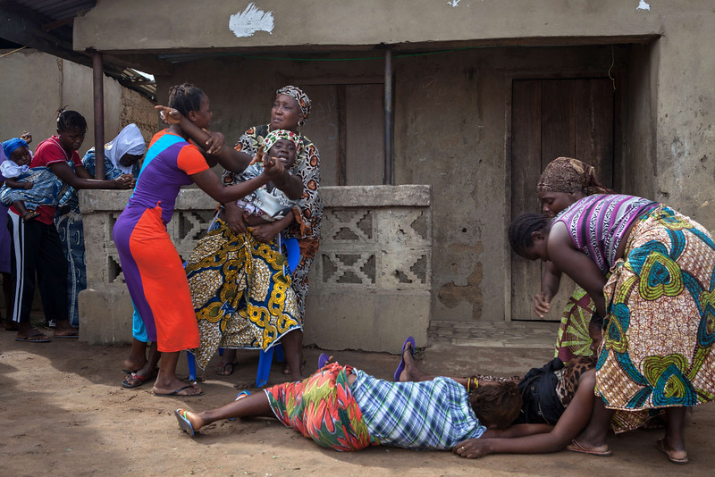 Description of  Women faint (Bottom) as another reacts while volunteers (unseen) take away from a nearby house the body of a woman who died of Ebola, in Waterloo, some 30 kilometers southeast of Freetown, on October 7, 2014. Dozens of British military personnel are due to fly to Sierra Leone next week to help build medical facilities to combat the Ebola epidemic, the defence ministry said on October 7.  AFP PHOTO / FLORIAN PLAUCHEUR