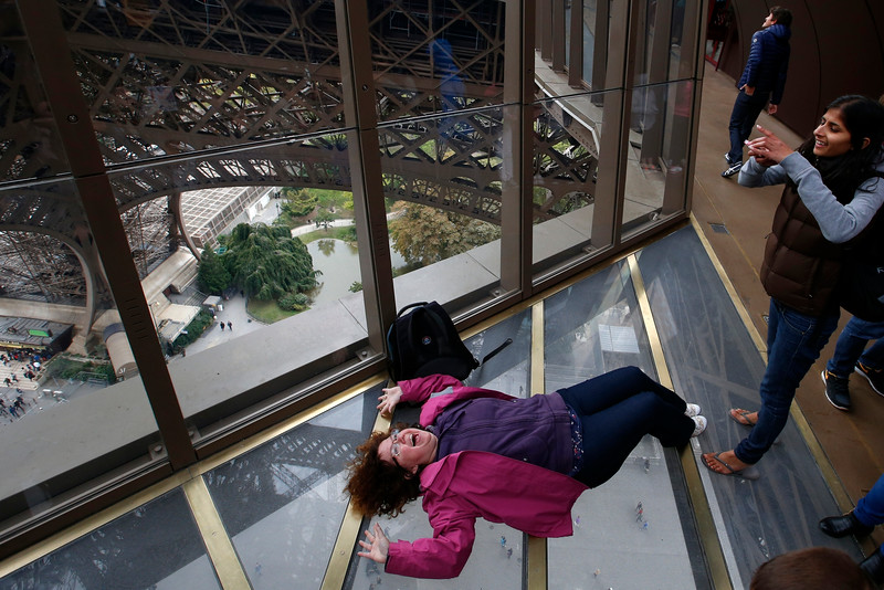 Description of  A Visitors takes a photo on the new glass floor at The Eiffel Tower, during the inauguration of the newly refurbish first floor, in Paris, France, Monday, Oct. 6, 2014. Visitors of the Eiffel Tower can walk on a transparent floor at 188 feet high and look down through solid glass, with safety glass barriers around the edge. (AP Photo/Francois Mori)