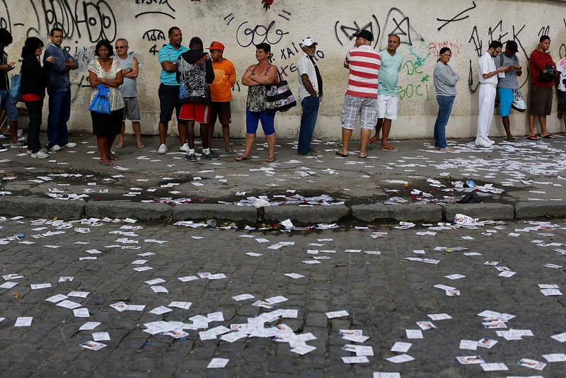 Description of  Campaign propaganda litters the street where people wait in line to vote in general elections outside a school in the Nova Holanda slum, inside the complexo da Mare in Rio de Janeiro, Brazil, Sunday, Oct. 5, 2014. Brazilians are casting ballots in a presidential election expected to force a three-week runoff campaign between incumbent Dilma Rousseff and one of her two top challengers. Brazilians are also deciding congressional races and electing governors. (AP Photo/Leo Correa)