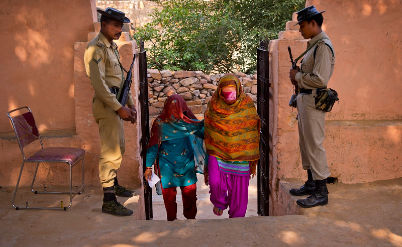 Description of  Security men guard as Indian women arrive to cast their votes during the Haryana state elections in Bandhwadi, India, Wednesday, Oct. 15, 2014. The Indian states Haryana and Maharashtra are going to the polls Wednesday to elect representatives to their respective state legislatures. (AP Photo/Saurabh Das)