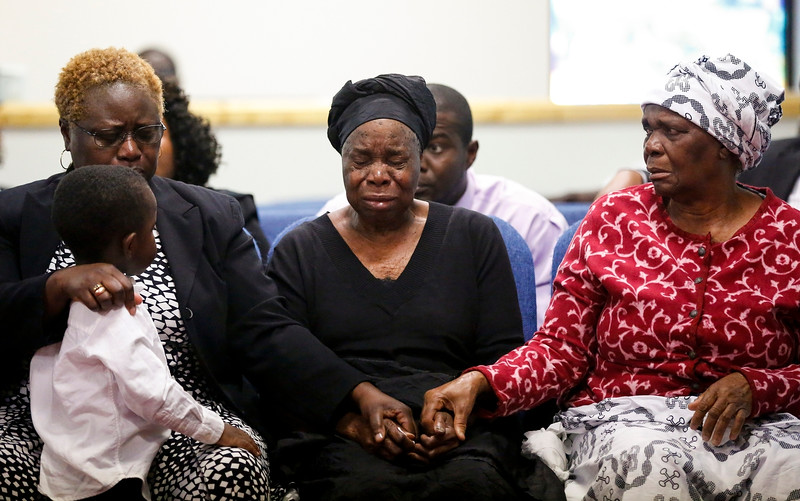 Description of  Garteh Korkoryah, center, mother of Thomas Eric Duncan, is comforted during a memorial service for her son, Saturday, Oct. 18, 2014, in Salisbury, N.C. Duncan died of Ebola in Dallas on Oct. 8. (AP Photo/Nell Redmond)