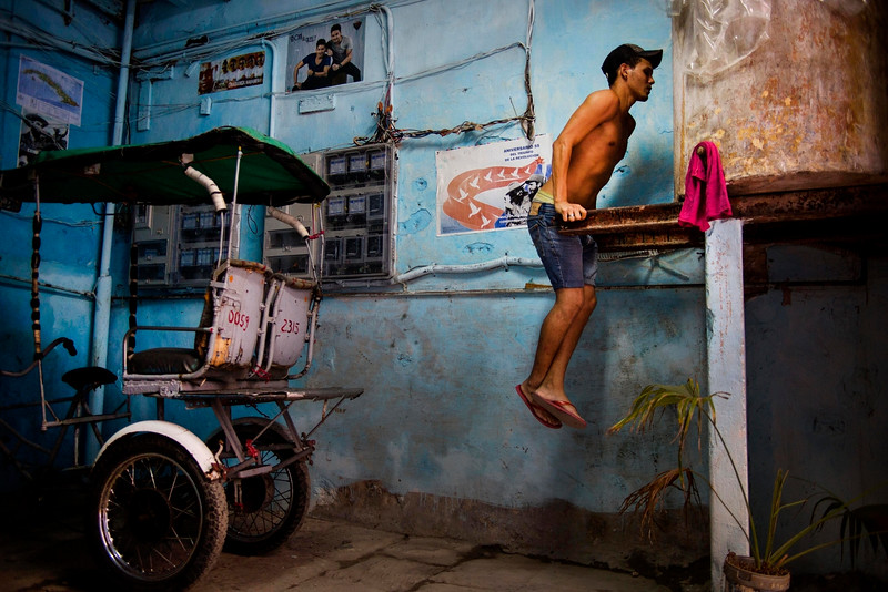 Description of  A young man exercises using the beams that hold a water tank at his house in Havana, Cuba, Monday, Oct. 13, 2014. (AP Photo/Ramon Espinosa)