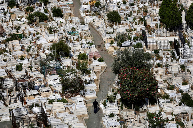 Description of  In this Oct. 14, 2014, photo, a Lebanese man, center, walks between graves at the overcrowded Bashoura cemetery for Muslim Sunnis in Beirut, Lebanon. The congested city of more than one million is cramped with cemeteries wedged into residential areas, increasingly forcing families to bury several members of the same family in one grave. Available land plots are extremely scarce and what is left is being used by developers to build luxury officers towers and apartments. (AP Photo/Hussein Malla)