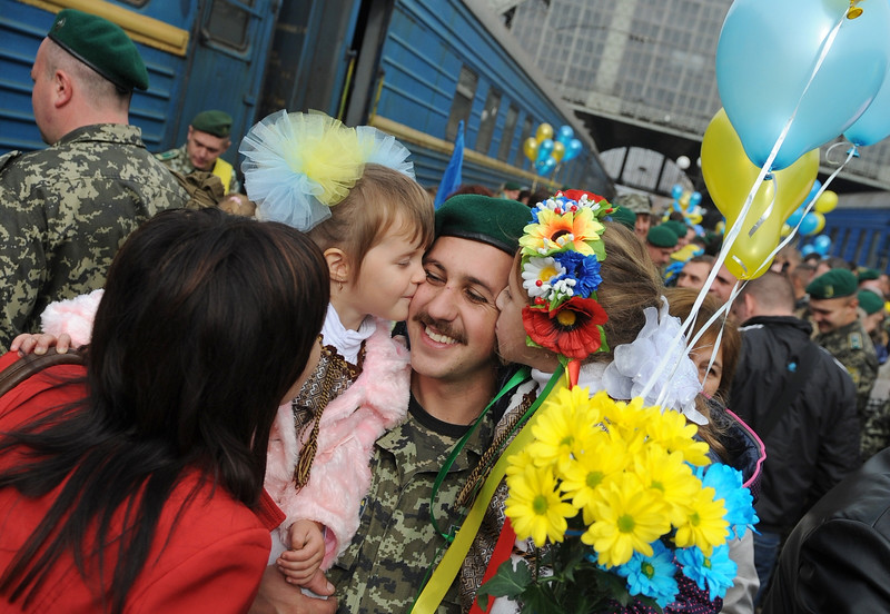 Description of  Ukrainian servicemen are greeted by relatives during a welcoming home ceremony in the western city of Lviv on October 16, 2014. Some 100 Ukrainian border guards returned home after serving a three-month mission on border with Russia in the Lugansk region of conflict-torn eastern Ukraine. AFP PHOTO / YURKO DYACHYSHYN