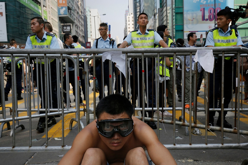 Description of  A protester sits front of barriers against police officers at a main street in Mong Kok district in Hong Kong Friday, Oct. 17, 2014. Riot police cleared an offshoot Hong Kong pro-democracy protest zone in a dawn raid on Friday, taking down barricades, tents and canopies that have blocked key streets for more than two weeks, but leaving the city's main thoroughfare still in the hands of the activists. (AP Photo/Vincent Yu)