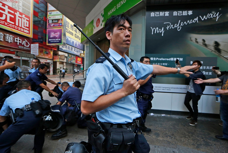 Description of  A police officer holding a police baton secures the area where a pro-democracy protester is being arrested by riot polices in the Mong Kok district of Hong Kong, early Friday, Oct. 17, 2014. Riot police moved in on a Hong Kong pro-democracy protest zone in a dawn raid on Friday, taking down barricades, tents and canopies that have blocked key streets for more than two weeks. (AP Photo/Kin Cheung)