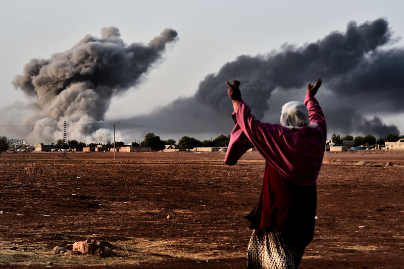 Description of  A woman reacts as smoke rises from the the Syrian town of Ain al-Arab, known as Kobane by the Kurds, after a strike from the US-led coalition as it seen from the Turkish - Syrian border in the southeastern village of Mursitpinar, Sanliurfa province, on October 13, 2014. AFP PHOTO / ARIS MESSINIS