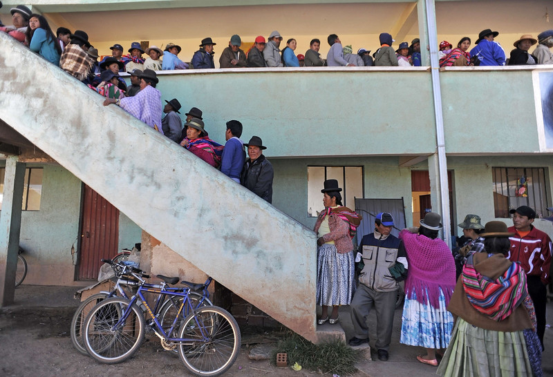 Description of  Citizens line up to vote at a polling station in the village of Laja, 36 km west of La Paz, in the highland Andean plateau, over 4,000 meters above sea level on October 12, 2014. More than six million Bolivians will elect their president for the next five years in an electoral process where voting is compulsory. AFP PHOTO/JORGE BERNAL