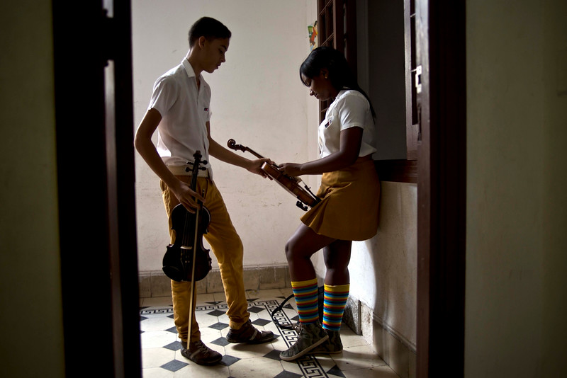 Description of  In this Oct. 9, 2014 photo, students tune their violins before class at the Manuel Saumell music school in Havana, Cuba. Before Cubaís 1959 revolution, many students played violins, violas, cellos and bass from European workshops. After it, the Soviet Union provided violins and cellos, along with many other goods. Now, as Cuba struggles to revive its economy, students must make do with violins from China that too easily pop strings and lose their tone. (AP Photo/Ramon Espinosa)
