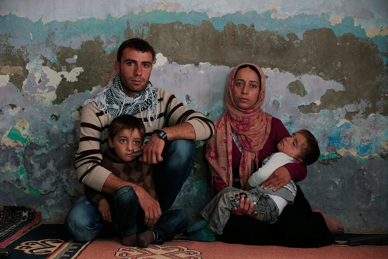 Description of  Syrian Kurdish fighter Delkhwaz Sheikh Ahmad, 22, sits with his wife Siham, 23, and their two sons, Dilyar, left, 3 and Ibrahim, 2, right, at his brother's house in Suruc, on the Turkey-Syria border, as he prepares to leave for Kobani, Syria, to rejoin the fighting, Friday, Oct. 17, 2014. Sheikh Ahmad is a member of the Peopleís Protection Units, also known as YPG and is fighting against militants of the Islamic State group in Kobani, Syria. Every few weeks, he takes a couple of days to cross the border into Turkey to visit his family that had evacuated. Kobani, also known as Ayn Arab, and its surrounding areas, has been under assault by extremists of the Islamic State group since mid-September and is being defended by Kurdish fighters. (AP Photo/Lefteris Pitarakis)