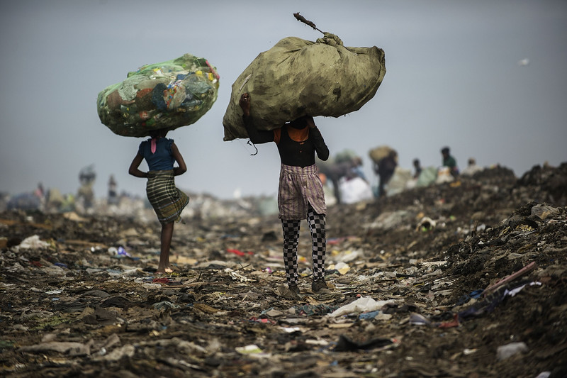 Description of  Girls carry bags of plastic items and tins as rubbish pickers sift through garbage at the Maputo municipal garbage dumping site in Maputo on October 14, 2014. Mozambique's upstart opposition vowed to take on the two traditional political heavyweights by offering a non-violent alternative in polls taking place on October 15 after a low-level conflict. AFP PHOTO/GIANLUIGI GUERCIA