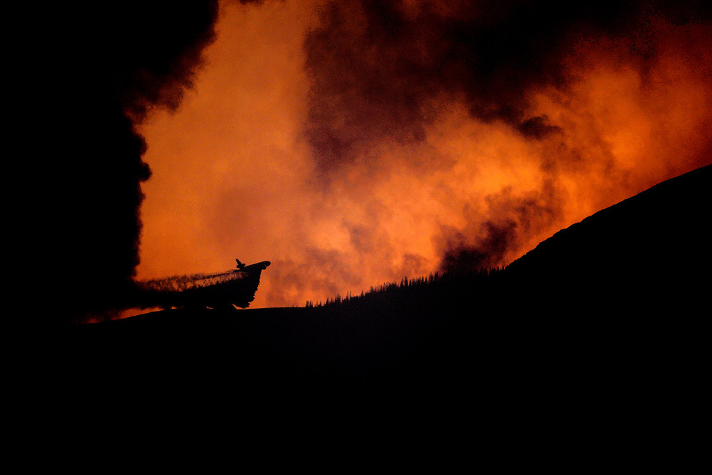. A plane drops slurry as the Papoose fire continues to burn at sunset near Creede, Colorado on June 25, 2013. The three fires that make up the West Fork Complex fire now top out at more than 70 thousand acres. (Photo by AAron Ontiveroz/The Denver Post)