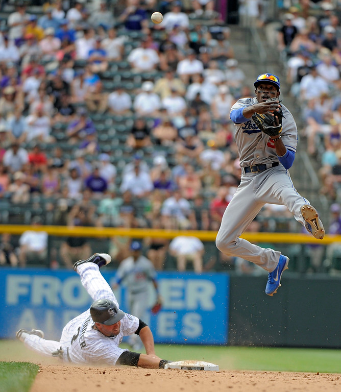 . Los Angeles Dodgers shortstop Dee Gordon (9) flies over a sliding Colorado Rockies right fielder Michael Cuddyer (3) to get the force and throw over to first in an attempt to get Colorado Rockies first baseman Todd Helton (17) at first base Sunday, June 3, 2012 at Coors Field.  Helton was safe on the play in the 8th inning. John Leyba, The Denver Post