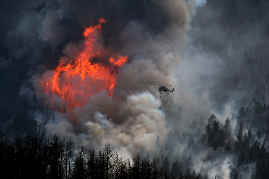 . A helicopter goes in to make a water drop as huge flames burn stands of trees on US Forest Service land on the Lime Gulch Fire off of Foxton Road near Conifer, Colorado on June 20, 2013. This new fire is burning near last year\'s Lower North Fork fire.  (Photo by Helen H. Richardson/The Denver Post)