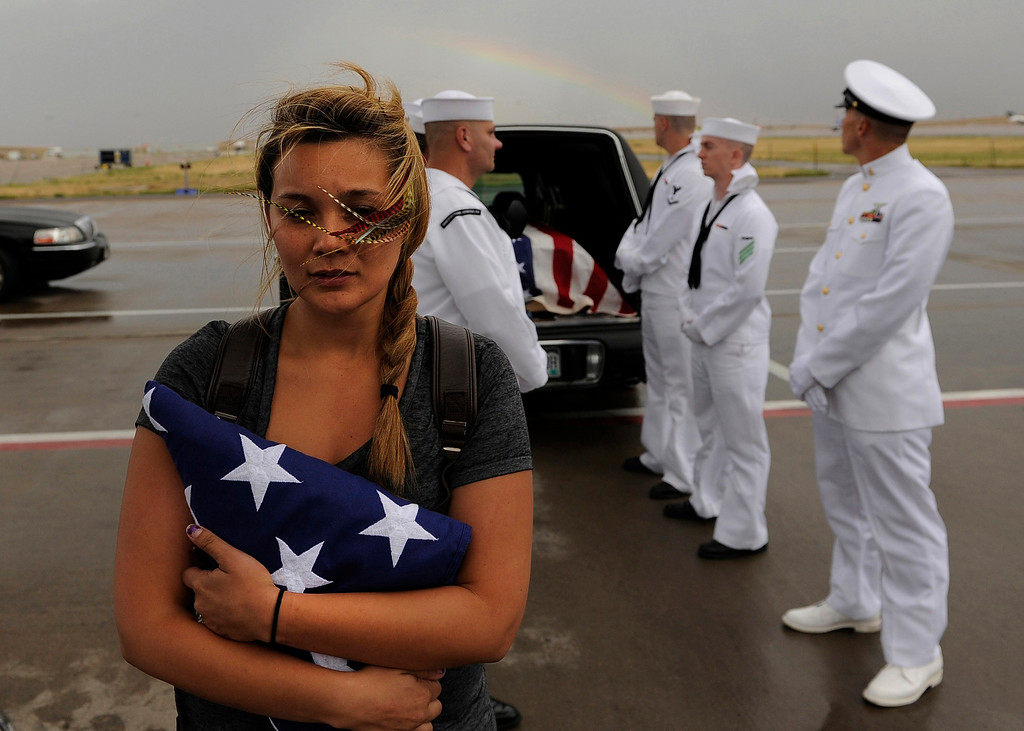 . Chantel Blunk, wife of Jonathan Blunk, waits Friday, July 27, 2012, on the tarmac at Denver International Airport as her husbands body is about to be loaded into a plane to fly to Reno Nevada for his full military funeral. Blunk a five-year U.S. Navy veteran that was killed during a July 20 shooting rampage at a movie theater in Aurora. (Photo by RJ Sangosti, The Denver Post)