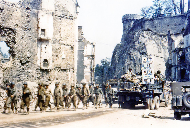 Description of  U. S. Army trucks and jeeps are driving through the ruins of Saint-Lo in July of 1944. A group of American soldiers walks along the street. The town was almost totally destroyed by 2,000 Allied bombers when they attacked German troops stationed there during Operation Overlord Normandy in June.  (Photo by Galerie Bilderwelt/Getty Images)