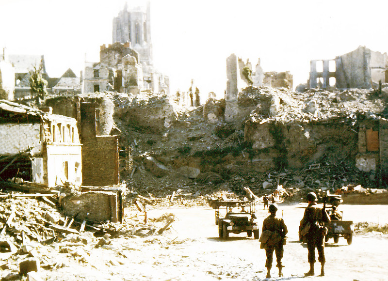 Description of  Two American soldiers watch U. S. Army jeeps driving through the ruins in Saint-Lo in August of 1944. The town was almost totally destroyed by 2,000 Allied bombers when they attacked German troops stationed there during Operation Overlord Normandy in June.  (Photo by Galerie Bilderwelt/Getty Images)