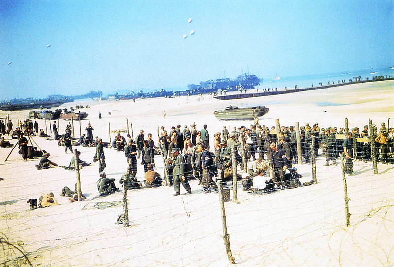 Description of  German Prisoners of War are kept behind barbed wire on Omaha Beach on June 10, 1944. Landing Ship, Tanks can be seen on the beach and barrage balloons in the air for protection.  (Photo by Galerie Bilderwelt/Getty Images)