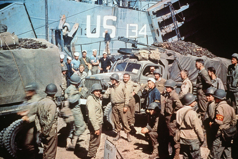 Description of  Trucks of the 1st Infantry Division of the United States Army are loaded into a Landing Ship Tank (LST) in Dorset, United Kingdom, on June 5th, 1944. The LST forms part of Group 30 of the LST Flotilla. The 1st Division was one of the two divisions that stormed Omaha Beach in Normandy, France on D-Day suffering high casualties. It secured Formigny and Caumont in the beachhead. D-Day is still one of the world's most gut-wrenching and consequential battles, as the Allied landing in Normandy led to the liberation of France which marked the turning point in the Western theater of World War II.  (AFP PHOTO/Getty Images)