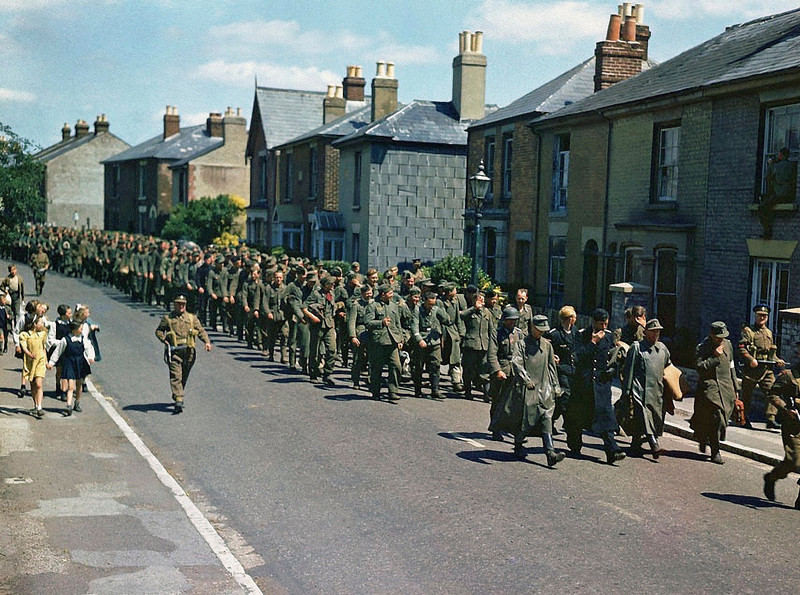 Description of  1,096 German Prisoners of War are marched through the town of Gosport, Hampshire, guarded by British soldiers, in June of 1944. The prisoners arrived on HM Landing Ship Tank (LST-165), the first transport with prisoners from the Allied invasion of Normandy. They will be interrogated and distributed to various camps according to their classification.  (Photo by Galerie Bilderwelt/Getty Images)