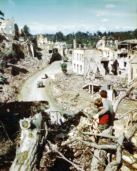 Description of  Two children watch an American Army jeep driving through the ruins of Saint-Lo in August of 1944. The town was almost totally destroyed by 2,000 Allied bombers when they attacked German troops stationed there during Operation Overlord Normandy in June.  (Photo by Galerie Bilderwelt/Getty Images)