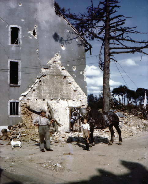 Description of  A farmer and his son in front of their damaged house during the Allied invasion of France in July of 1944. Bombing of German positions caused damage throughout the area.  (Photo by Galerie Bilderwelt/Getty Images)