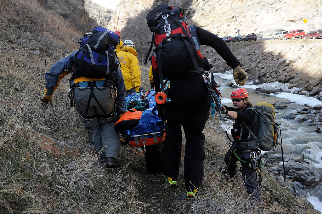 Description of . GOLDEN, CO - FEBRUARY 16: Alpine Rescue Team Field Director Tom Wood acts as a human barrier to keep people from falling off a narrow trail as members of the Alpine Rescue Team carrie out a litter holding the
