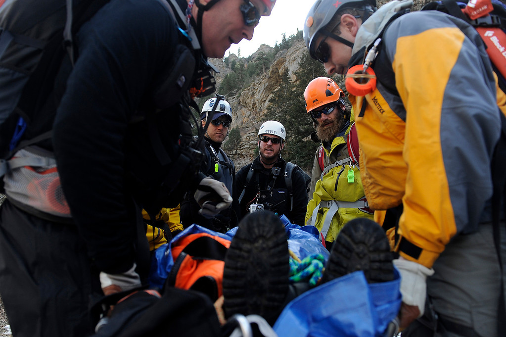 Description of . GOLDEN, CO - FEBRUARY 16: Scott Franey, center, of the Alpine Rescue Team coordinates his team before transporting a