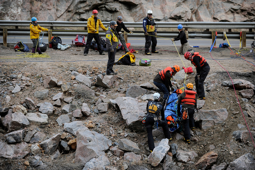 Description of . GOLDEN, CO - FEBRUARY 16: Members of the Alpine Rescue Team carry out a litter holding the