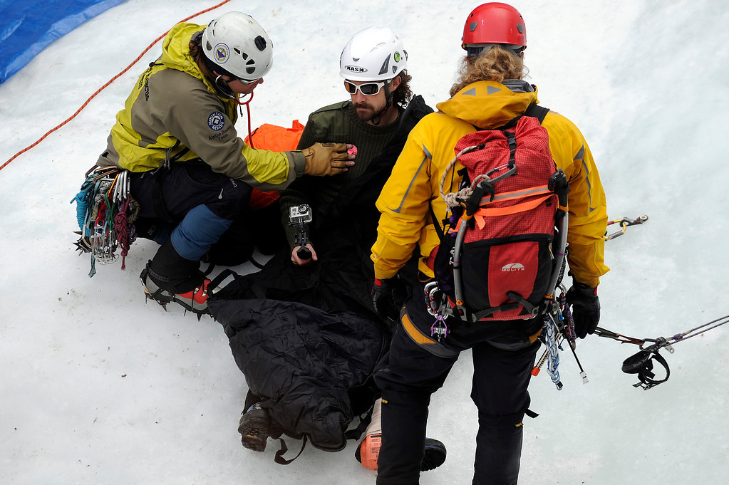 Description of . GOLDEN, CO - FEBRUARY 16:  Zach Taylor, left, checks Charlie Adams vital signs during an ice climbing rescue training by the Alpine Rescue Team in Clear Creek Canyon near Golden, Colorado on February 16, 2014. The Alpine Rescue Team is one of a handful of nationally accredited mountain rescue team in Colorado. They specialize in rescue services in hard-to-reach areas and conditions. (Photo by Seth McConnell/The Denver Post)