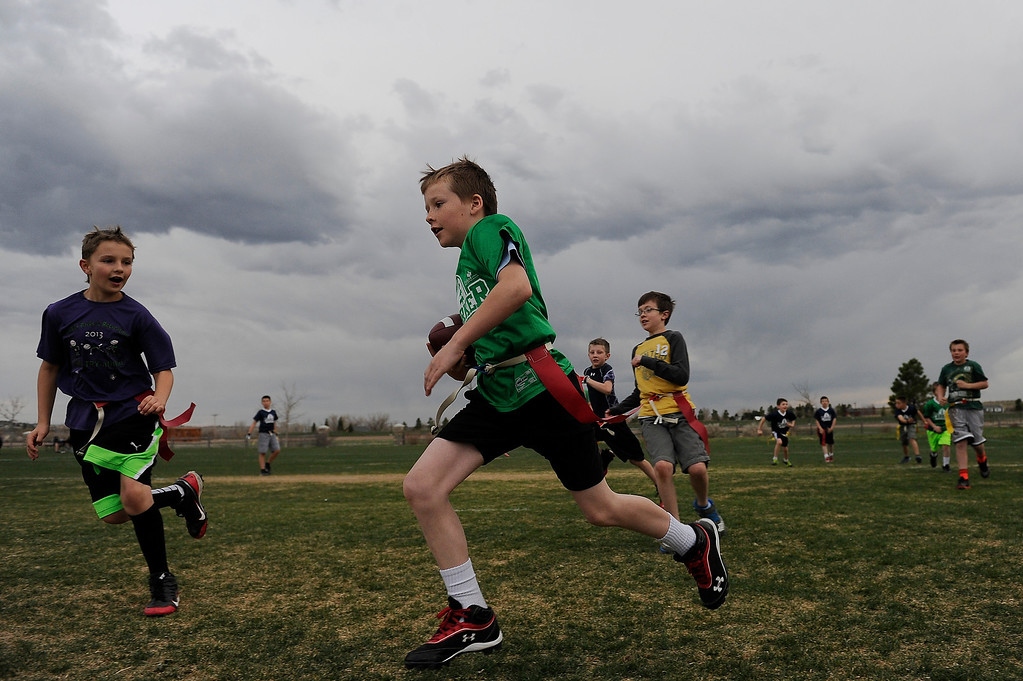 Description of . PARKER, CO - APRIL 18: Johnny Seely sprints past a defender as he runs up field during flag football practice at Salisbury Equestrian Park and Sports Complex in Parker, Colorado on April 18, 2014. Parker recently purchased 90 acres north of the existing Salisbury Equestrian Park and Sports Complex and are looking for feedback for possible uses. (Photo by Seth McConnell/The Denver Post)