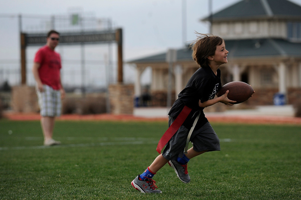 Description of . PARKER, CO - APRIL 18: Harrison Dishong, 7, catches a pass from his dad, Scott Dishong, as he warms up before flag football practice at Salisbury Equestrian Park and Sports Complex in Parker, Colorado on April 18, 2014. Parker recently purchased 90 acres north of the existing Salisbury Equestrian Park and Sports Complex and are looking for feedback for possible uses. (Photo by Seth McConnell/The Denver Post)