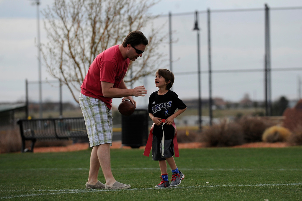 Description of . PARKER, CO - APRIL 18: Scott Dishong tells his son, Harrison Dishong, 7, which route to run as they play catch before flag football practice at Salisbury Equestrian Park and Sports Complex in Parker, Colorado on April 18, 2014. Parker recently purchased 90 acres north of the existing Salisbury Equestrian Park and Sports Complex and are looking for feedback for possible uses. (Photo by Seth McConnell/The Denver Post)