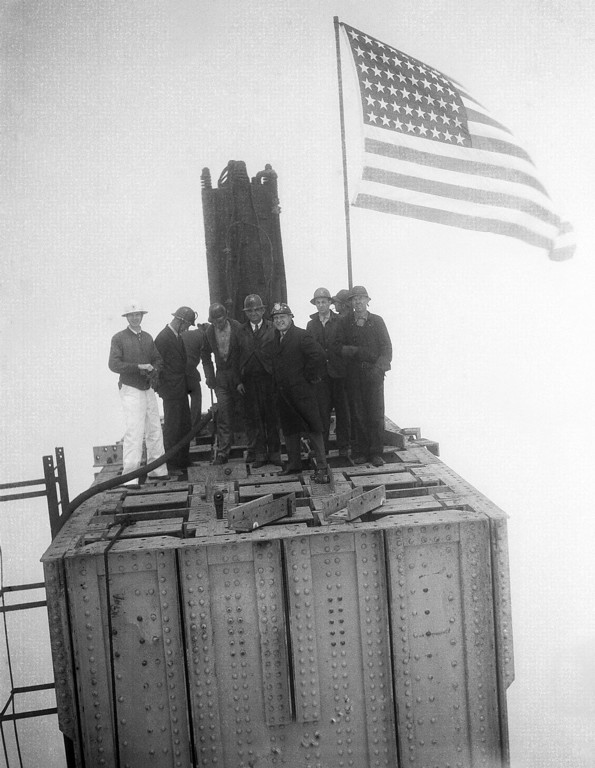 Description of . High in the fog, structural steel workers staged the traditional ceremony of raising flags when the structural steel work on the Marin County Towers of the Golden Gate Bridge, San Francisco was completed, May 4, 1934. Group of steel workers atop one of the two towers which rise 734 feet above the water. (AP Photo)