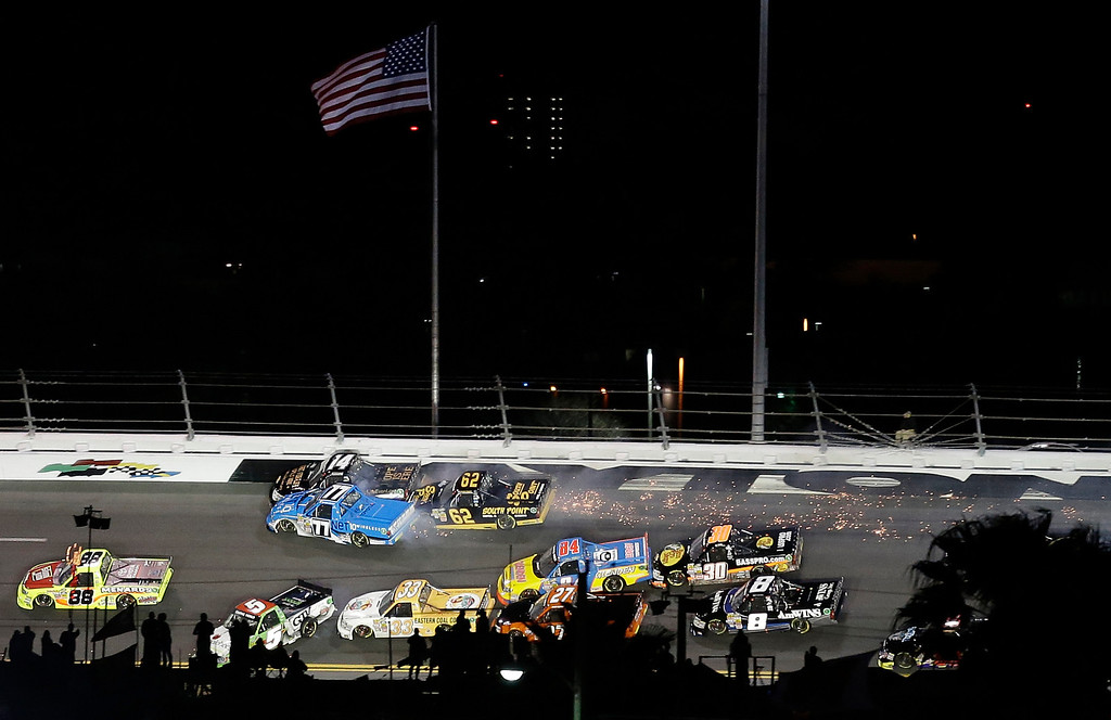 Description of . Trucks, including those driven by Brennan Newberry (14); German Quiroga (77), of Mexico; and Brendan Gaughan (62), crash going into Turn 3 during the NASCAR Truck Series auto race at Daytona International Speedway, Friday, Feb. 22, 2013, in Daytona Beach, Fla. (AP Photo/Chris O'Meara)