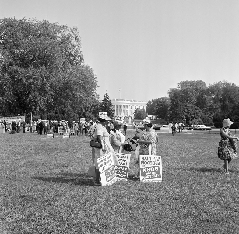 Description of . Members of the United Automobile Workers delegation pick up signs on the Ellipse for March on Washington demonstration on August 28, 1963. In background is White House. (AP Photo)