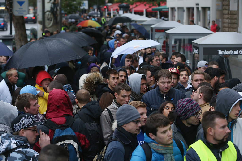 Description of . People line up outside the Berlin Apple Store to buy the new Apple iPhone 5S and 5C smartphones on the first day of sales on September 20, 2013 in Berlin, Germany. The new iPhone 5S and 5C phones went on sale all over the world today and hundreds of customers waited outside the Berlin store in the rain to be among the first to buy the new phones starting at 8am.  (Photo by Sean Gallup/Getty Images)