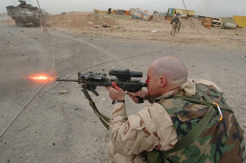 Description of . Although wounded, Staff Sgt. Shannon Kay, of 1st Battalion, 24th Infantry Regiment, fires on an enemy position after being attacked with a car bomb, Saturday, Dec. 11, 2004, in Mosul, Iraq. (AP Photo/Army Times, M. Scott Mahaskey, via USA Today)