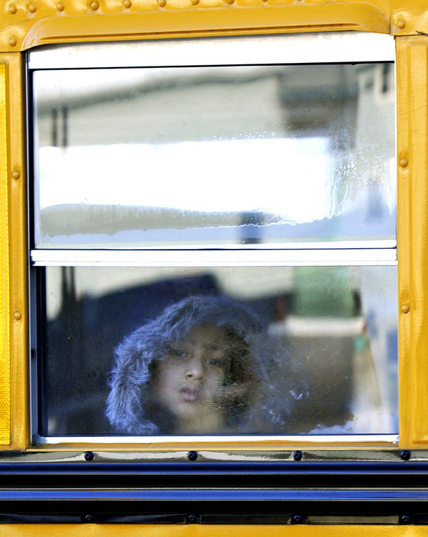 Description of . A Sandy Hook Elementary student leaves on a school bus  in Newtown, Connecticut on January 3, 2013.  Students at the elementary school where a gunman massacred 26 children and teachers last month were returning Thursday to classes at an alternative campus described by police as