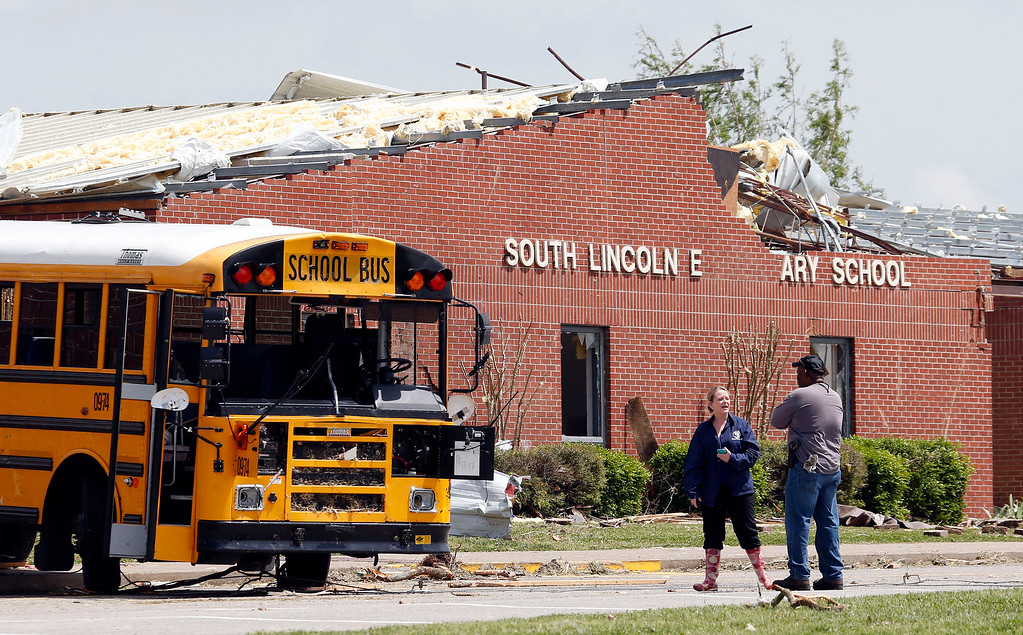 Description of . Workers view damage at South Lincoln Elementary School on Tuesday, April 29, 2014, after storms came through Monday in Fayetteville, Tenn.  (AP Photo/Mark Humphrey)