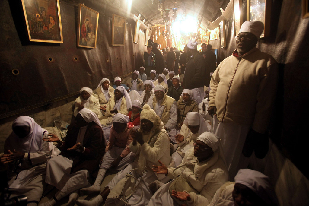 Description of . Christian pilgrims pray at the Church of the Nativity, traditionally believed to be the birthplace of Jesus Christ, during Christmas celebrations in the West Bank biblical town of Bethlehem on December 24, 2013.  Palestinian president Mahmud Abbas urged Christian pilgrims from around the world to visit the Holy Land to mark the visit of Pope Francis, set for 2014, in a Christmas message.   HAZEM BADER/AFP/Getty Images