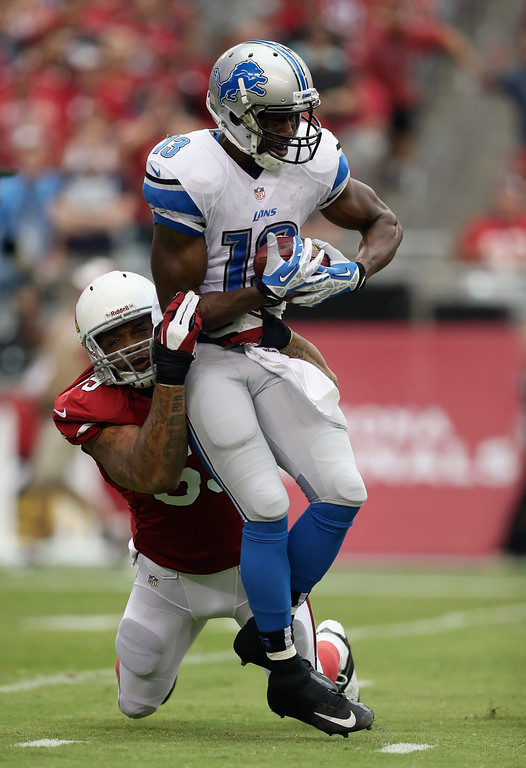 Description of . Wide receiver Nate Burleson #13 of the Detroit Lions is hit for a loss by defensive end John Abraham #55 of the Arizona Cardinals in the first quarter at University of Phoenix Stadium on September 15, 2013 in Glendale, Arizona.  (Photo by Jeff Gross/Getty Images)